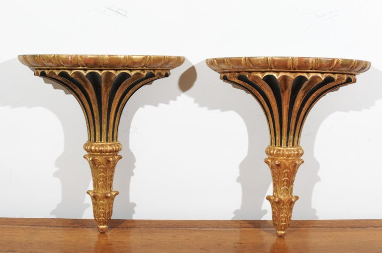 A pair of Italian painted and carved wall brackets from the late 19th century, with black and gold accents. Born in Italy during the third quarter of the 19th century, each of this pair of wall brackets features a flared gilded body presenting a