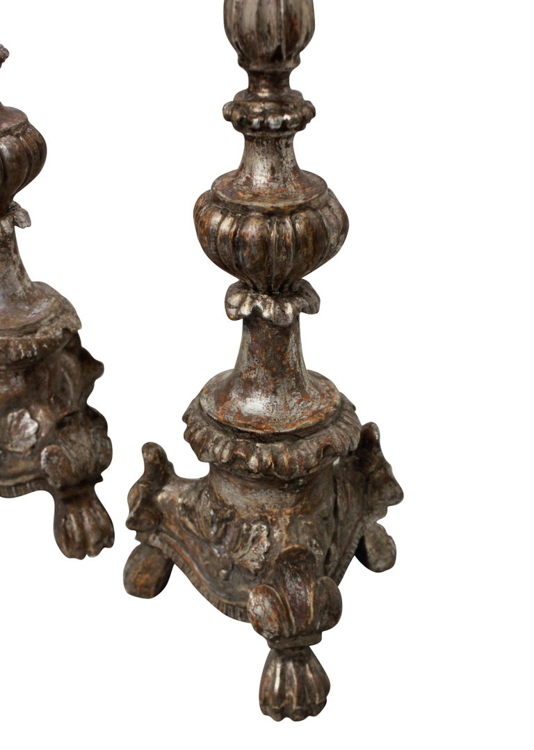 A pair of Italian 18th century, carved and silver leaf candlesticks as lamps.