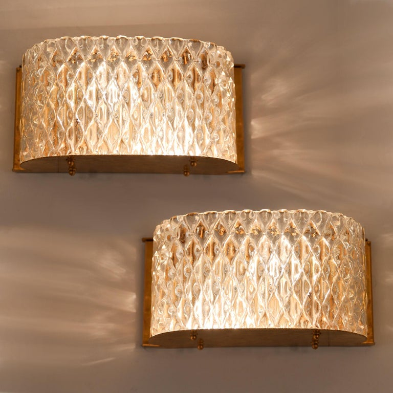 Glamorous criss-cross textured glass wall light with curved corners. The overall effect of the glass alongside the reflection of the brass back plate and base creates a lovely diffused warm light.