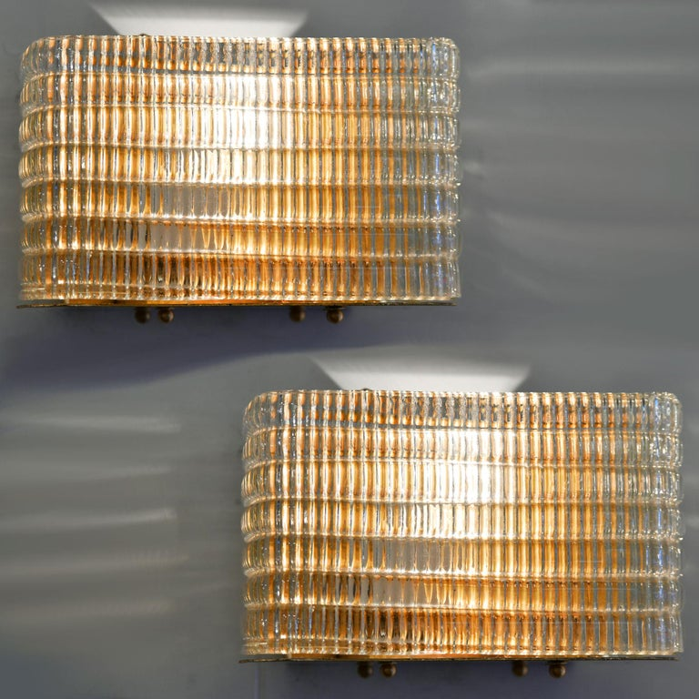 Glamorous wall light with curved corners. Six layers of textured glass, the vertical ribbing effect is on the inside whilst the outside is horizontal shape in layers. The overall effect of the glass alongside the reflection of the brass back plate