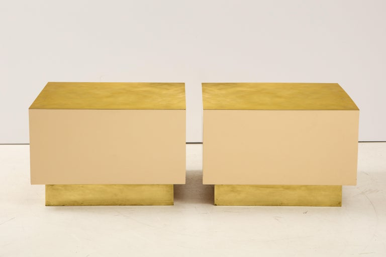 A pair of Italian 1970s brass and lacquer cube form coffee or cocktail tables; Minimalist and chic. The body is a creamy warm white lacquer, supported on a brass inset base and with brass surface: a color scheme that feels inherently glamourous.