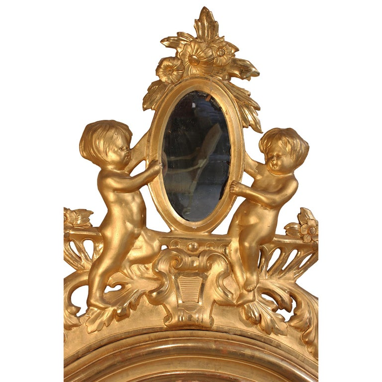 A spectacular pair of Italian 19th century giltwood mirrors. The rectangular moulded framed mirrors with curved top and pierced central reserve adorned by two charming cherubs displaying an oval mirror with flowers. Flanked by large scrolled