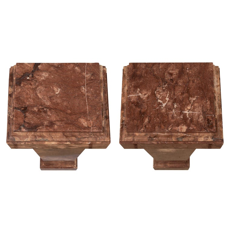 A beautiful pair of Italian 19th century neoclassical style rouge marble pedestal columns. Each column is raised by a square base with a fine mottled border. The elegant lightly tapered square central supports display decorative cut corners while
