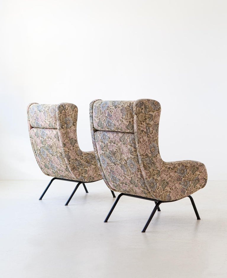 Set of two Italian lounge chairs, manufactured during the 1950s  The black enameled iron tubular legs are a Classic of modern design of the 1950s, in the seat of the armchair you can read a search for beauty and sculptural details, the design is