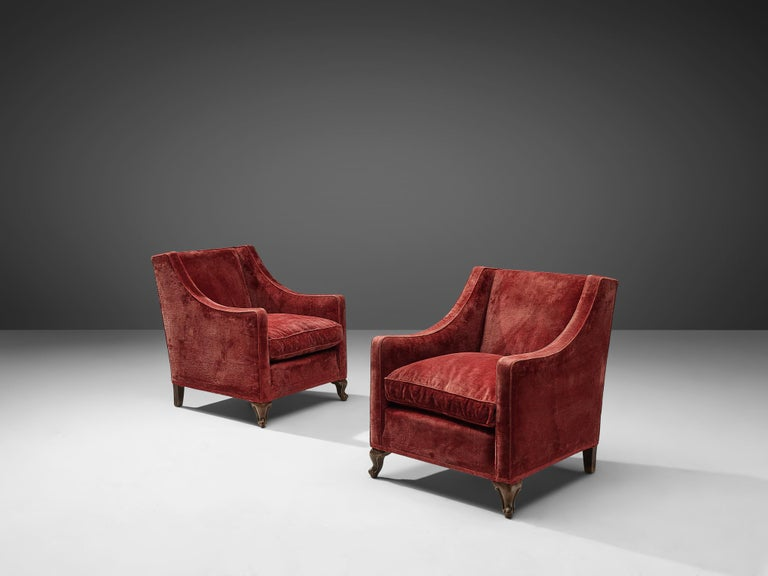 Set of two armchairs, red velour upholstery, hard wood, Italy, 1930s  Two Classic easy chairs with soft velour upholstery. The chairs are highly comfortable and have a sturdy appearance. When seated you experience a pleasant enclosed feeling due to