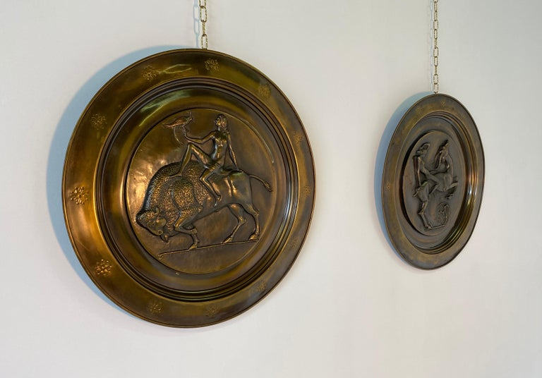 Pair of hanging brass plates produced in Italy in the 1940s. The Classic Art Deco subjects are represented and are in their original patina of the time. Small signs of wear due to age.