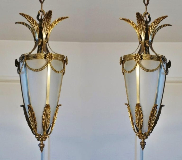 Pair of Art Deco lanterns, Italy 1930s. Solid bronze and parcel brass with cone-shaped frosted glass shade. Each lantern: One single E7 light socket for a large size bulb, 60W - 100W. Dimensions: Total height with chain: 41