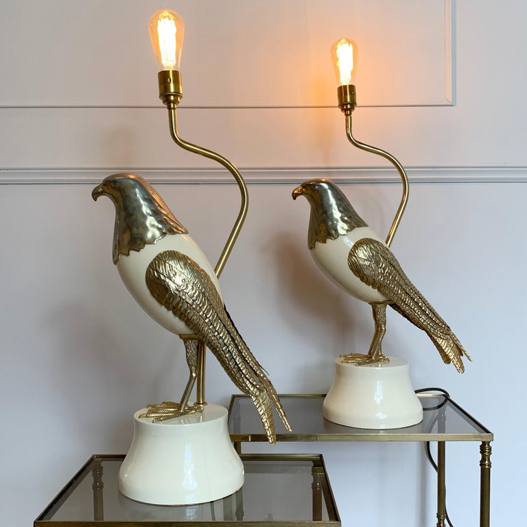 A stunning and bold statement pair of Italian bird of prey table lamps, circa 1960s Italian Large lamps, 65.5cm height, 34cm width, 20cm depth, bird approx 48cm length Cream toned wood with gold toned metal work on heavy wooden base These lamps