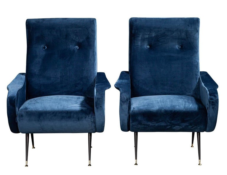 Pair of Italian blue velvet lounge chairs Attributed to Zanuso Style. Classic mid-century modern styling, featuring original blue velvet upholstery. Finished with a sleek stain black metal leg.  Price includes complimentary curb side delivery to