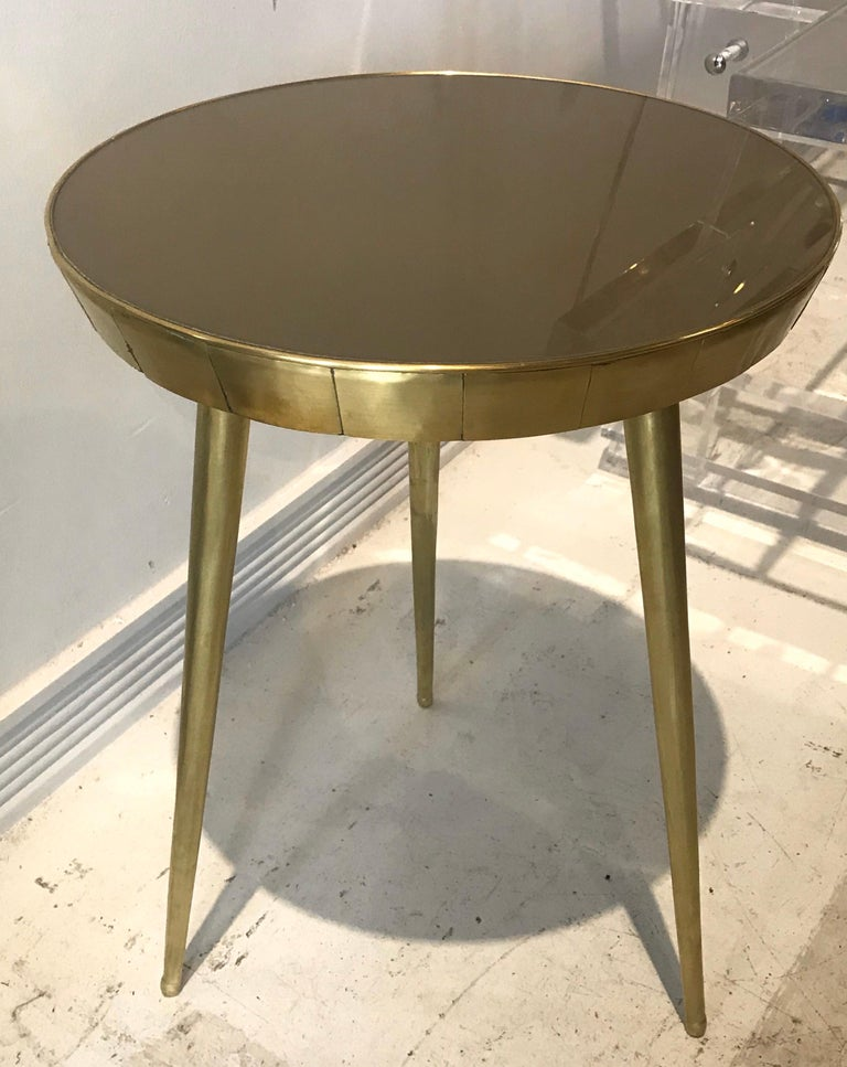 A pair of chic reverse painted (toffee colored) glass and brass Italian side tables.