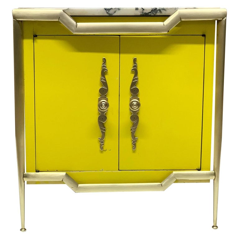 Pair of Italian brass cabinets with marble tops. The cabinets are wood with a yellow painted finish. Has brass frames and decorative brass hardware with an adjustable glass shelf inside. Style of Tommi Parzinger.