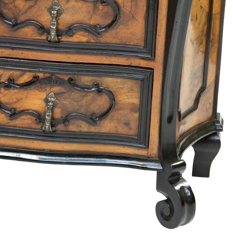 A pair of burl wood side chest of drawers. These chests are petite in size. The chests are quality reproductions made from old wood and in the style of furniture from Milan. They have ebonized wood accents and burl olive wood patched veneer. A