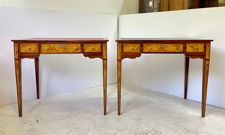 Fabulous and intricate pair of 20th century neoclassical writing desks or side tables styled in burl wood veneers and string inlays. Each has a tooled and inset leather top over a frieze holding three drawers with brass knobs and a scalloped apron.