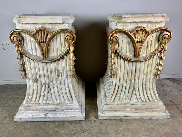 Pair of Italian carved painted and parcel gilt pedestals with parcel gilt details depicting a shell motif with garlands hanging from scrolled ends.