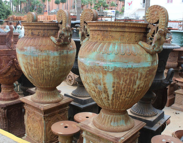 Pair of massive Italian antico green cast iron urns with fluted decorations, women and lions handles.