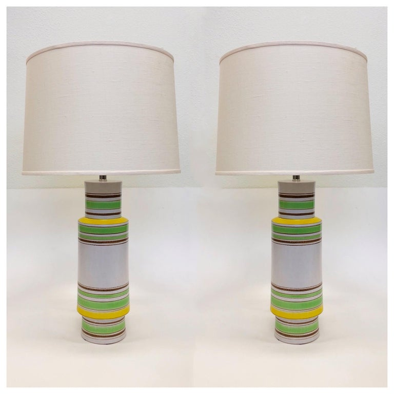 A beautiful pair of Italian ceramic table lamps designed by Bitossi in the 1970s The lamps are ceramic with a white, lime green, yellow and brown glazed design. The lamps have been newly rewired with new polish nickel hardware and new vanilla linen