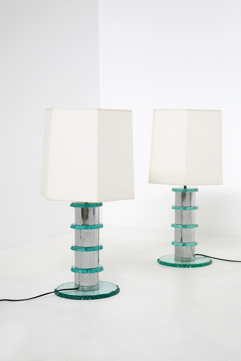 Elegant pair of contemporary Italian lamps. The lamps are made in Italy by master glassmakers. The lamp is handmade. The stem of the lamp is made of chrome plated steel and at each intersection we notice hammered glass circles applied. As a support