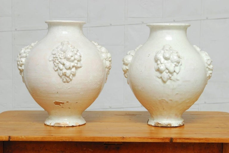 Pair of rustic Italian earthenware pottery jars with a bulbous urn form body and fruit clusters cascading down the tapered base. Featuring a thick cream ware glazing that has a rich craquelure finish. Est. circa 1900, these jars have chips and