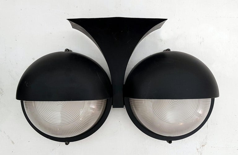 A pair of black wall sconces in cast aluminium made for exterior use. Each sconce has two heavy set pieces of glass concealing a lightbulb each. Will work with screw in lightbulbs. Some scuff marks which is visible in the pics.
