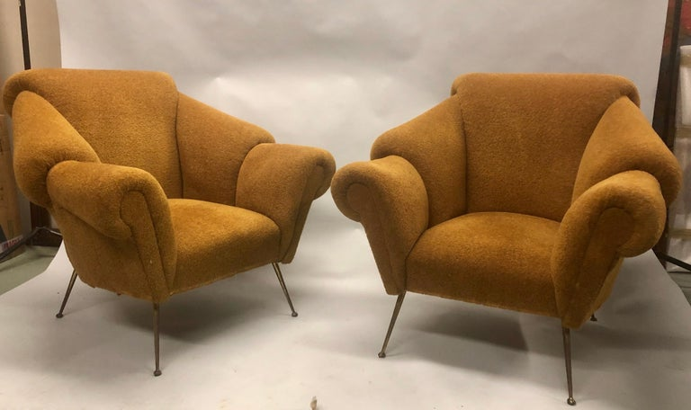 Rare and original pair of Italian Futurist lounge chairs / armchairs / wingback style chairs attributed to Giacomo Balla with stunning layered, sequential arms that convey speed and continual movement.  The pair is set upon tapered brass legs.