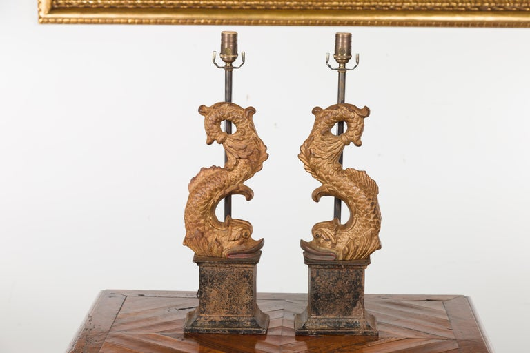 A pair of Italian gilt iron Baroque style dolphin sculptures from the early 20th century, made into lamps and mounted on tall bases. Created in Italy during the first quarter of the 20th century, each of this pair of sculptures features a dolphin