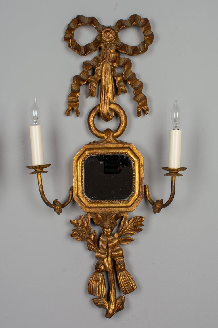 A pair of Italian Palladio style gilded wood two-light candle sconces with framed mirrors. Carved with ribbons, swags, and tassels with warm gilt finish. Each with two gilded metal candle arms. Electrified with new sockets and a ground wire will