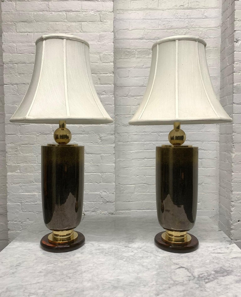 Pair of Italian glass lamps. Lamps are brass, well designed with a nice brown glass color. Also has a Bakelite base. Shades not included.