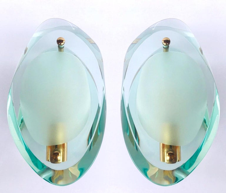 Stunning pair of Italian Mid-Century Modern Murano glass sconces. Sconces are fitted with thick beveled glass plates with organic forms. The translucent jeweled glass has a green colored cast featuring sandblasted centers and polished edges. Sconces