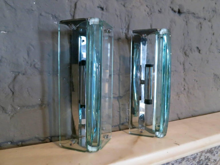 A smart pair of sconces in the manner of Fontana Arte, with chrome fitting and thick cut curved glass diffusers.