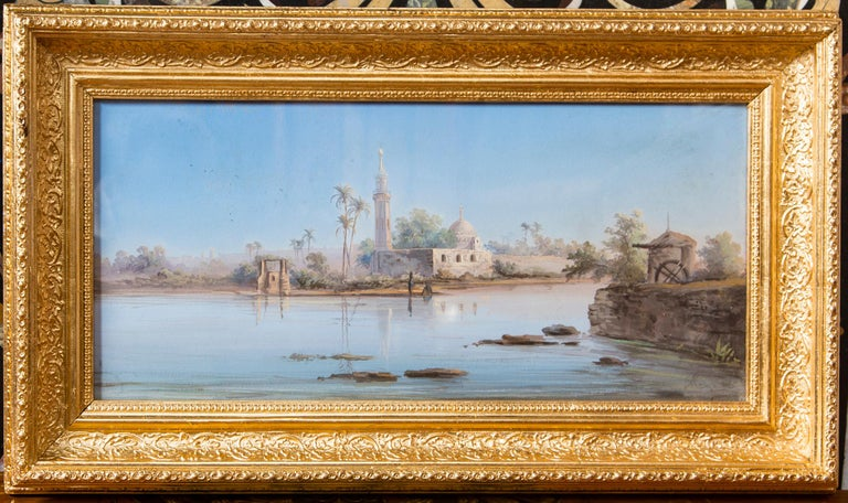 Set within newly gilded wood frames. Each is illegibly signed. One of figures seated and standing along a lake or riverbank. Dwellings and palm trees in the background. The other  of  a   minaret  and other  structures.
