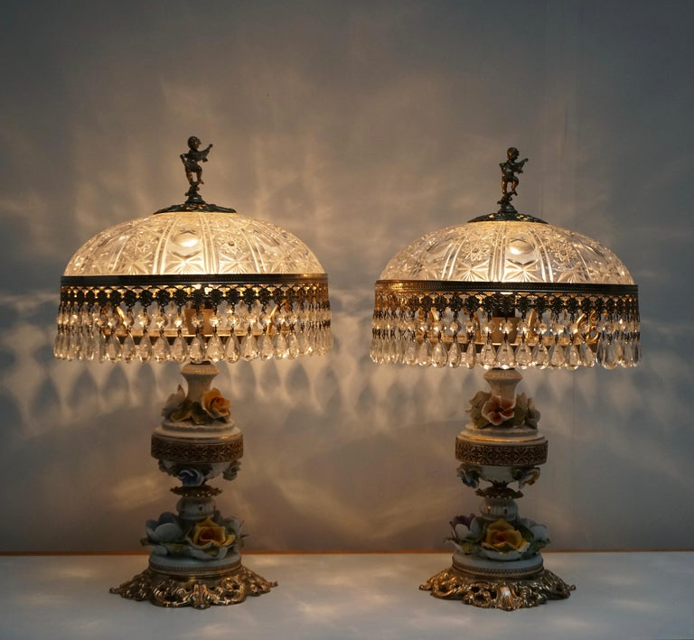 Two table lamps with a crystal shade and brass base decorated with porcelain flowers. Measures: Diameter 32 cm. Height 52 cm.