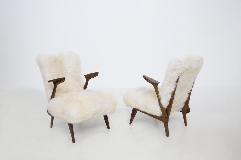 Elegant pair of Italian armchairs attributed to Giuseppe Scapinelli from the 1950s. The armchairs are made of walnut wood. The armchairs have a linear and anthropomorphic shape where the armrest vibrates towards each other with triangular shape .