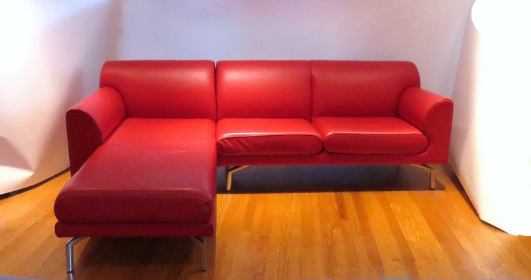 Pair of vibrant red leather sofas by Poltrona Frau from the EOS series, made in Italy, circa early to mid-2000s. The sofas are mirror images of one another. The chaises can be unhooked from the two-seat element of the sofa, and reconfigured to make