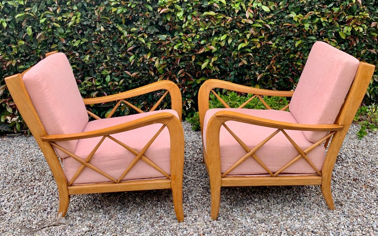 A pair of Italian lounge chairs, by Paolo Buffa and upholstered in hand sewn Rose hued Pierre Frey Linen. The pair are exquisitely designed with chic, yet bold detailing - from the subtle carved wood, to the crossed arm details. The European pair