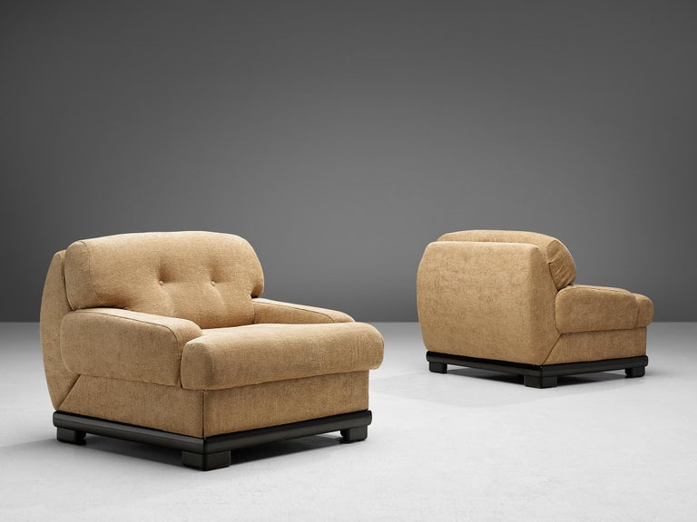 Set of two lounge chairs, fabric and lacquered wood, Italy, 1950s.  Italian set of opulent armchairs with tufted backrests.These chairs are the pinnacle of lush and comfort thanks to the chunky shaped backrests and low armrests. The chairs feature