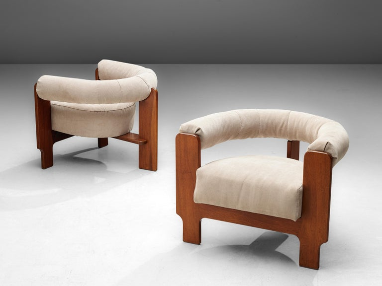 Set of two lounge chairs, mahogany and cream colored upholstery, Italy, 1960s.  Set of two Italian armchairs with mahogany frames. The wooden angular frame contrasts with the soft round shaped upholstered backrest and the comfortable seating pillow.