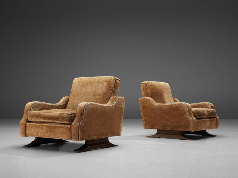 Pair of lounge chairs, darkened oak, velvet, Italy, 1950s  Gorgeous pair of lounge chairs made in Italy. The chairs have a sturdy yet elegant design. This is mainly thanks to the curved edges of the seats of the armrests. These decorated lines are