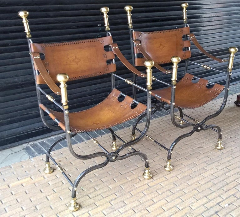 A pair of Italian Savonarola style polished wrought iron and brass embellished leather bound late 20th century open armchairs.