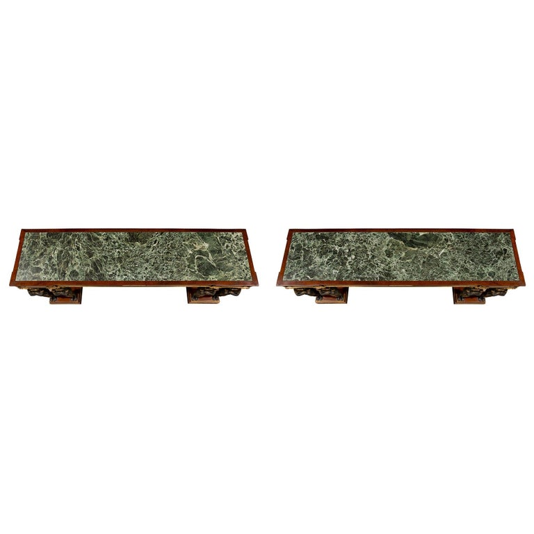 A sensational pair of Italian mid-19th century Empire style freestanding flamed mahogany consoles from Naples, Italy. The consoles are raised by double mottled rectangular bases with brass edges. Each flamed mahogany console is supported by