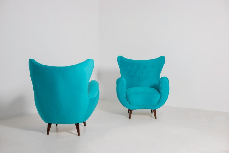 Elegant pair of Italian midcentury armchairs from the 1950s. The pair of armchairs has been restored in an elegant and refined Italian blue velvet. The peculiarity of the seat is its enveloping semi-curved backrest that gives a perfect harmony to