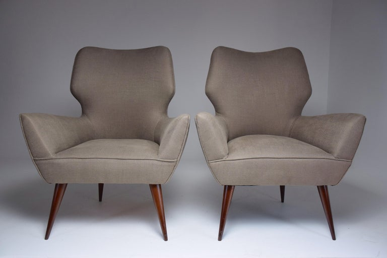 Set of 20th-century vintage Italian armchairs crafted in typical Italian midcentury style with the curved backrest and splayed, tapered wooden legs. In fully restored condition with a grey upholstery. Italy, circa 1950s.