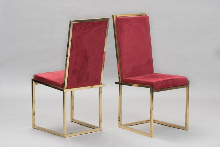 A pair of high back chairs in brass and bordeaux suede.