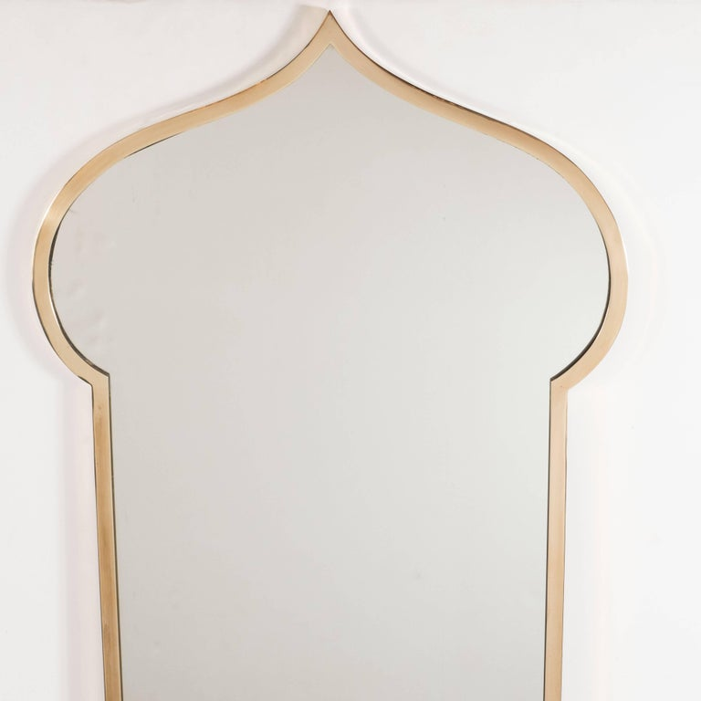 This handsome and refined pair of Mid-Century Modern mirrors were realized in Italy, circa 1960. They feature rectangular bodies that dramatically expand outwards near their apex creating rounded sides and then receding to point. This bell-shaped