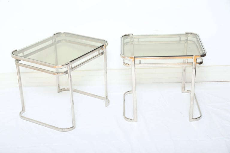Pair of sleek midcentury side tables with streamline design. The tables feature curved corners with double banded frames and curved legs or bases. The tables have a small rectangular form and be used horizontally or vertically. Fitted with smoked