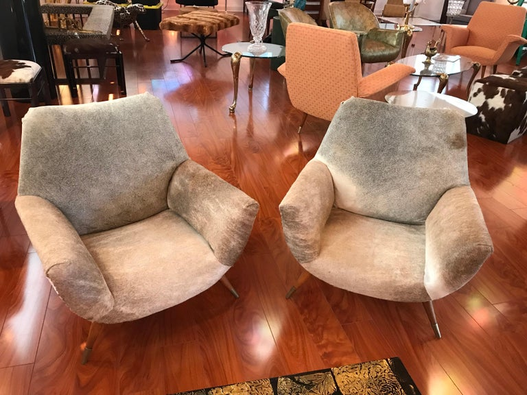 A pair Italian Mid-Century Modern club chairs covered in cow hide having nailheads, circa 1960. These are great for any room and the cowhide is in amazing condition. The club chairs are a little lower to the floor with a Seat height of 12.5 inches.
