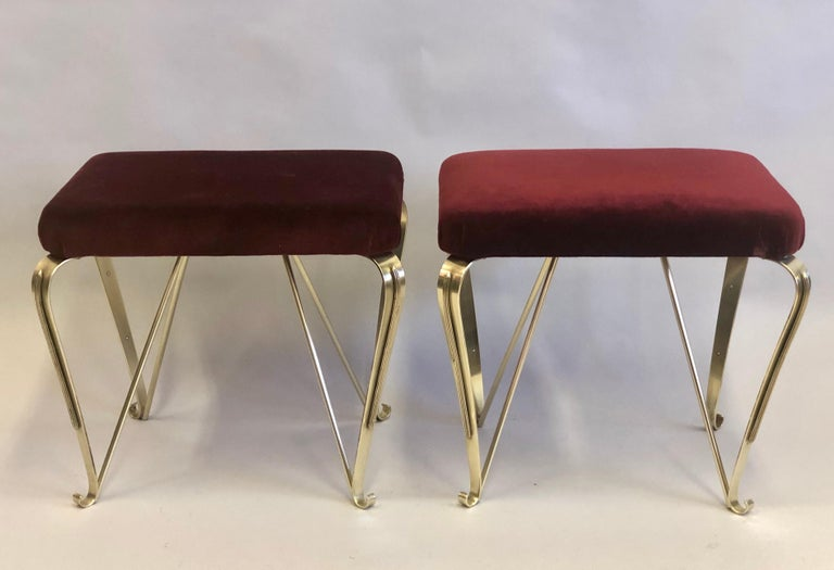 Elegant and rare pair of Italian Mid-Century Modern neoclassical benches / stools in solid brass with upholstered seats by Maison Jansen  The structure is composed of solid brass featuring 4 legs splayed on an angle and tapered delicately; they