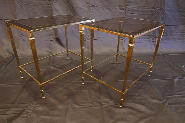 Pair of Italian gilt-brass Mid-Century Modern side tables with glass tops, (circa 1970s). These elegant tables feature glass tops that are slightly Smokey with silvered bands around the perimeter, and simple fluted legs tapering to the feet.