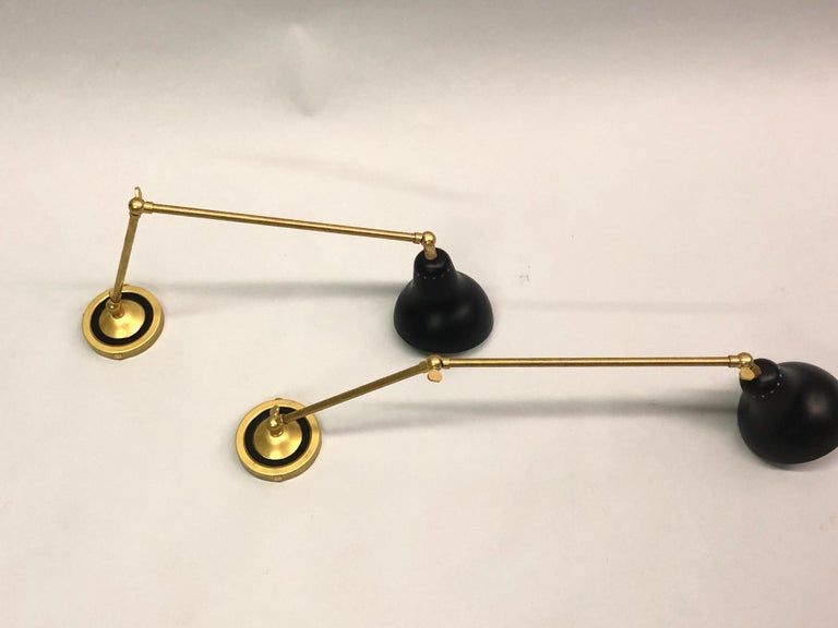 Pair of Italian Mid-Century Modern style articulating wall lights in solid brass and black enameled metal in the style of Angelo Lelli for Arrredoluce. Set up for 1 European candelabra socket per shade  Other references: Gino Sarfatti, Arteluce,