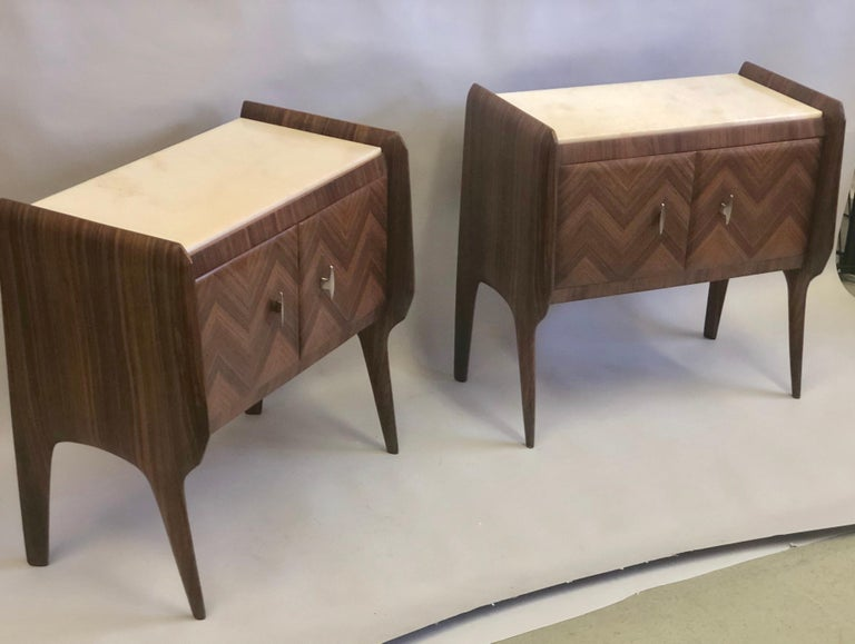 Pair of Italian Mid-Century Modern nightstands / end tables / side tables attributed to Osvaldo Borsani.  Inlaid mahogany in chevron pattern with white marble tops. Doors open and contain storage.