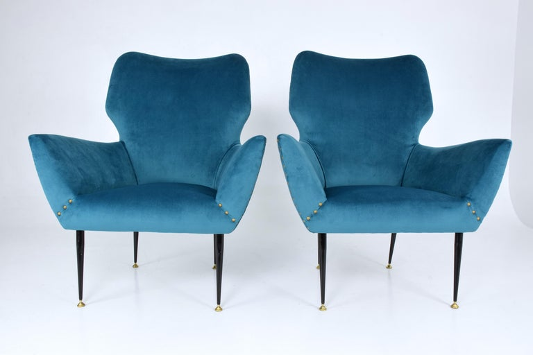 Pair of 20th century vintage Italian armchairs with a curved silhouette frame and tapered steel legs with polished brass endings. We have restored the chairs with blue velvet upholstery, new padding and nailhead trim.   This staple style of Italy's,